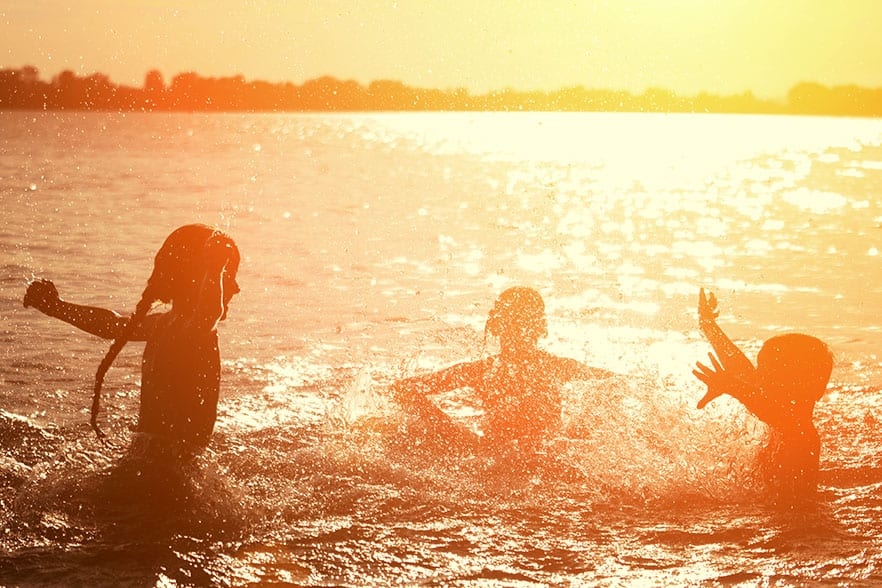Children playing in a lake at sunset