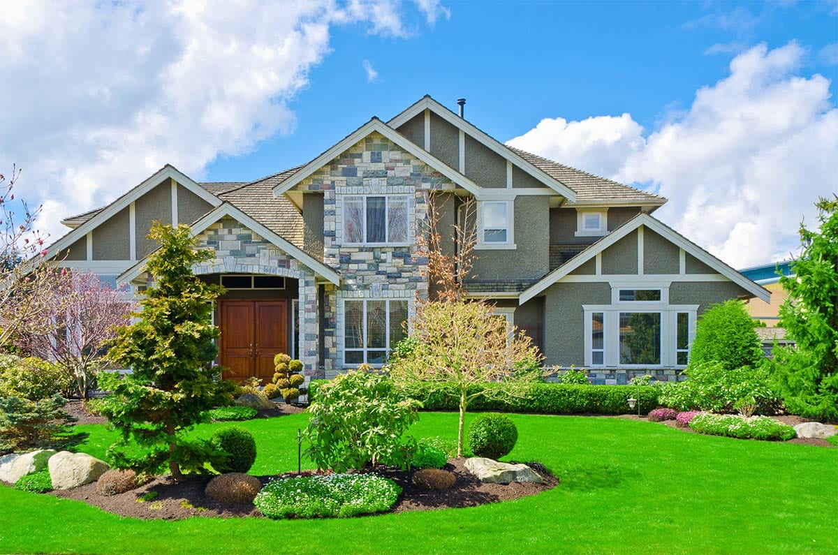 A large home with a healthy green lawn