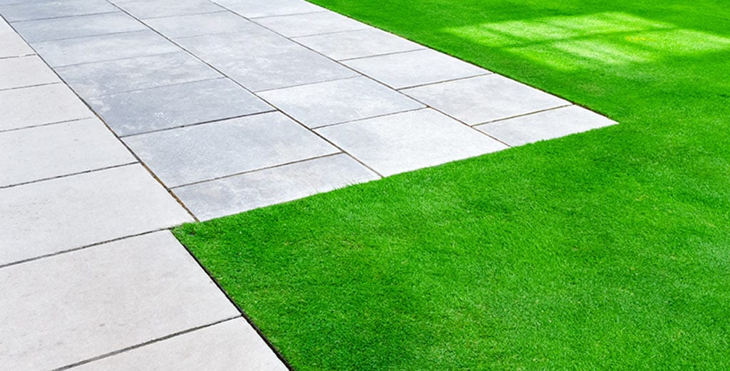 a paver patio and a healthy lawn