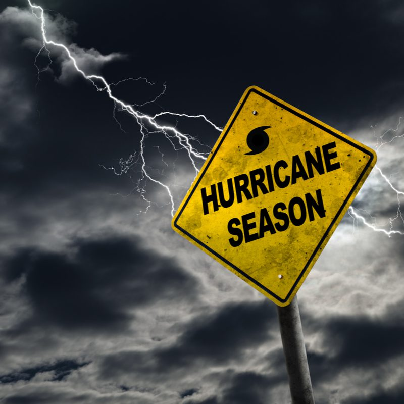 sign saying hurricane season with storm behind it